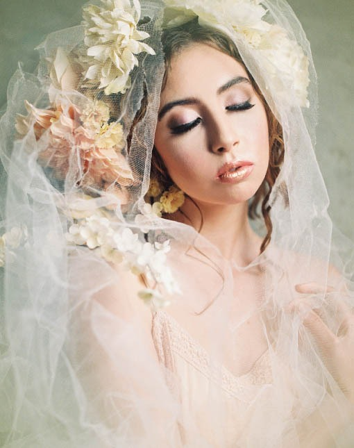 Female model wearing floral headpiece and white veil.