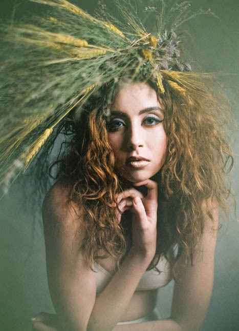Young female model wearing dramatic headpiece with flowers and wheat.