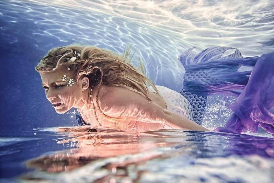 Blonde model wearing a purple mermaid costume underwater.