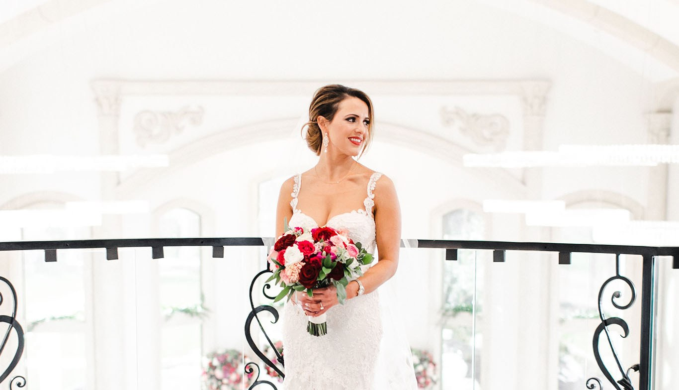 Attractive Brunette holding a bouquet of roses in a wedding dress while standing in front of a metal bannister indoors.