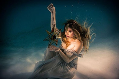 Girl underwater holding a gold and glass star from a metal string.  She is wearing a thin sheet and her hair is flowing in the water.