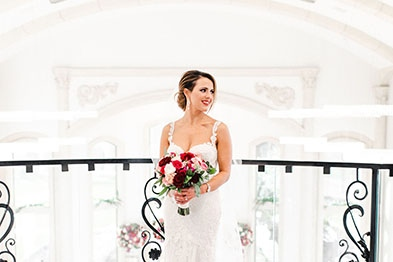Girl in a wedding dress standing in front of a banister holding a bouquet of different colored roses.