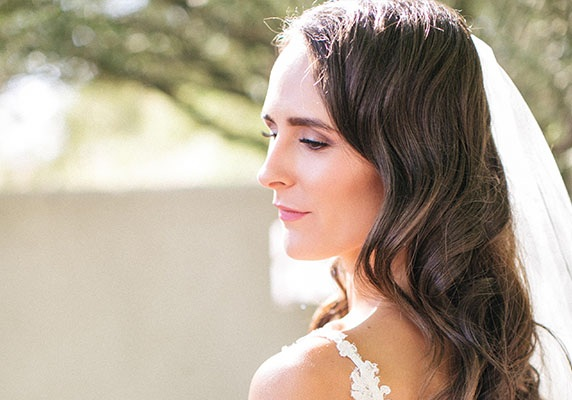Brunette girl in a wedding dress and veil looking away from the camera while standing outside.