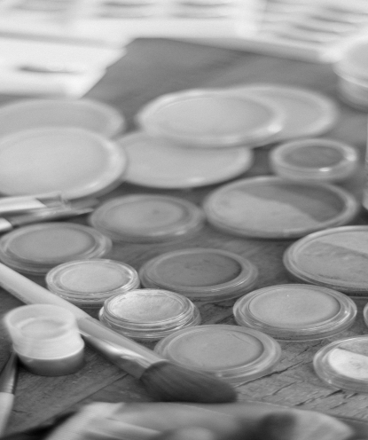 Faded background image of several palettes of foundation and other types of makeup.