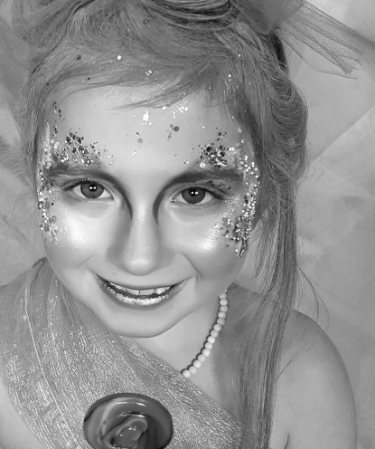 Faded background image of a young girl with glittery makeup smiling at the camera.